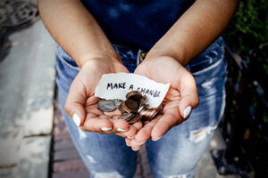 "a woman's cupped hands full of various coins and a piece of paper that says, ""mage a change""."