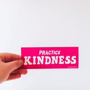 "a hand holding a pink sign that says ""Practice Kindness"""